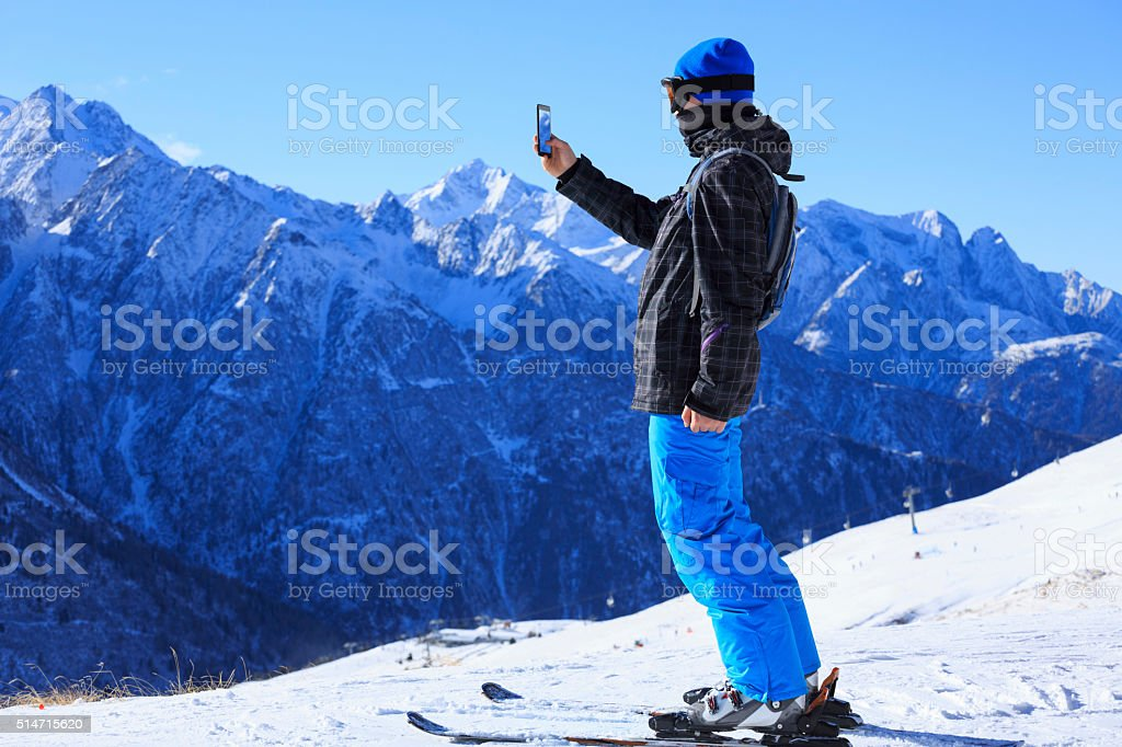 Snow skier teens boy photographing winter landscape  Uses touchscreen smartphone stock photo