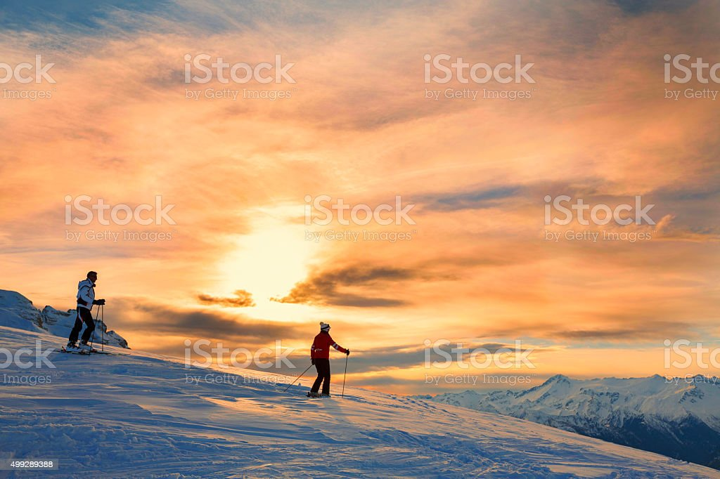 Snow skiers couple  Enjoying a beautiful winter mountains  sunset landscape stock photo