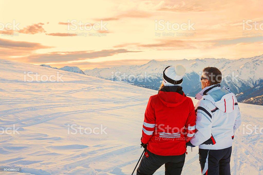 Snow skiers couple  Enjoying a beautiful winter mountains  sunset landscape stock photo