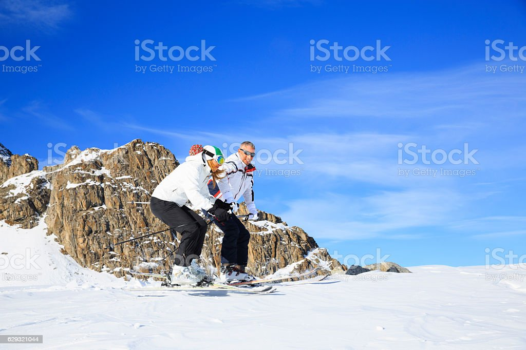 Snow skiers  Couple man and woman skiing  Sunny ski resort stock photo