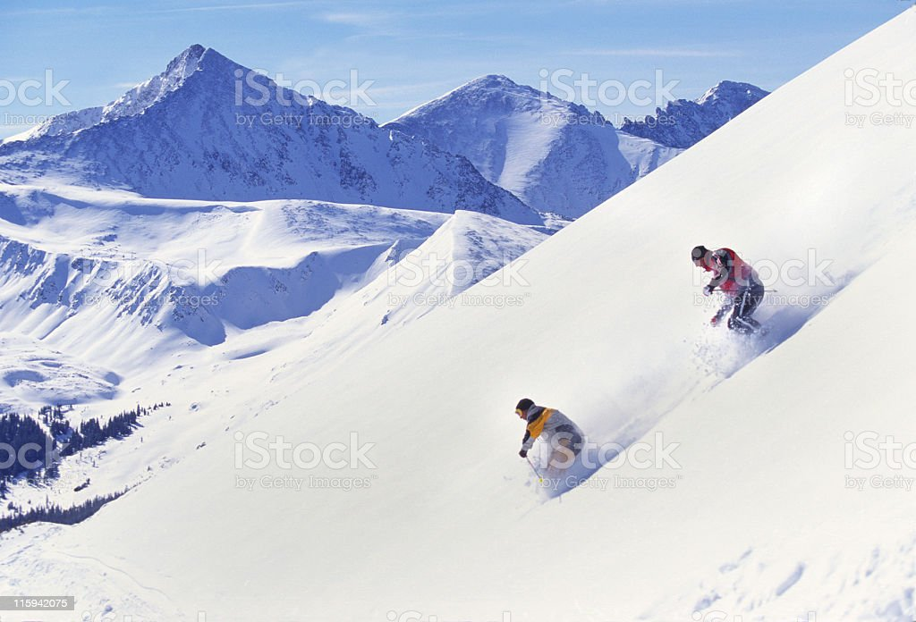 Snow Skiers in Fresh Powder with Mountain View royalty-free stock photo