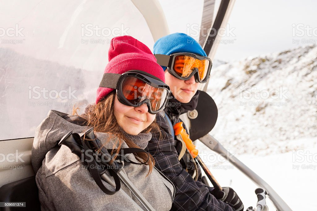 Snow skiers teenagers girl and boy on the ski lift stock photo