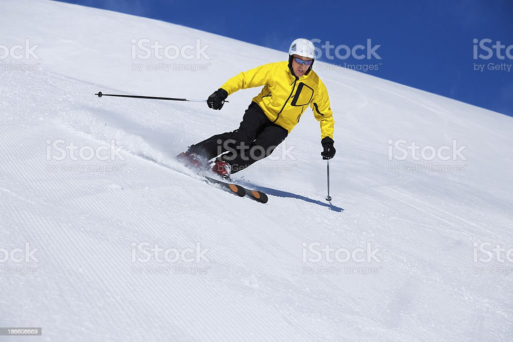 Snow skier, skiing carving at high speed, mountain ski resort in the...