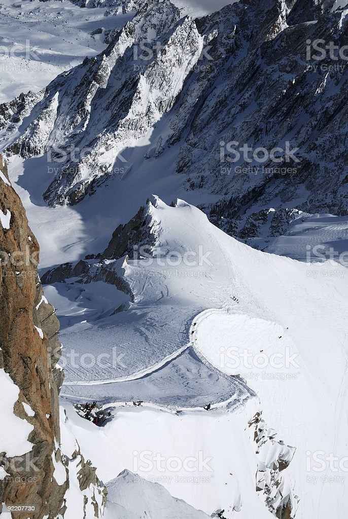 Snow slope with skiers between mountain ranges royalty-free stock photo