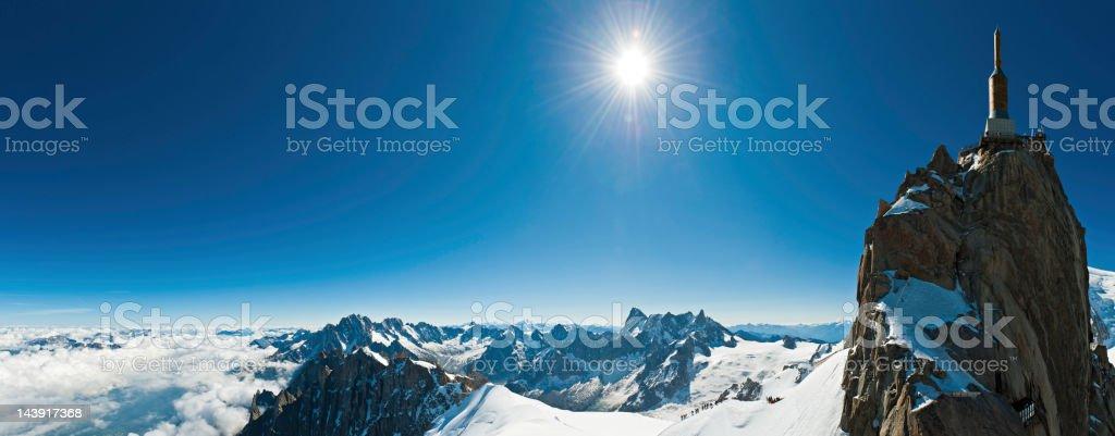 Snow summit sunburst Alpine cable car station panorama stock photo