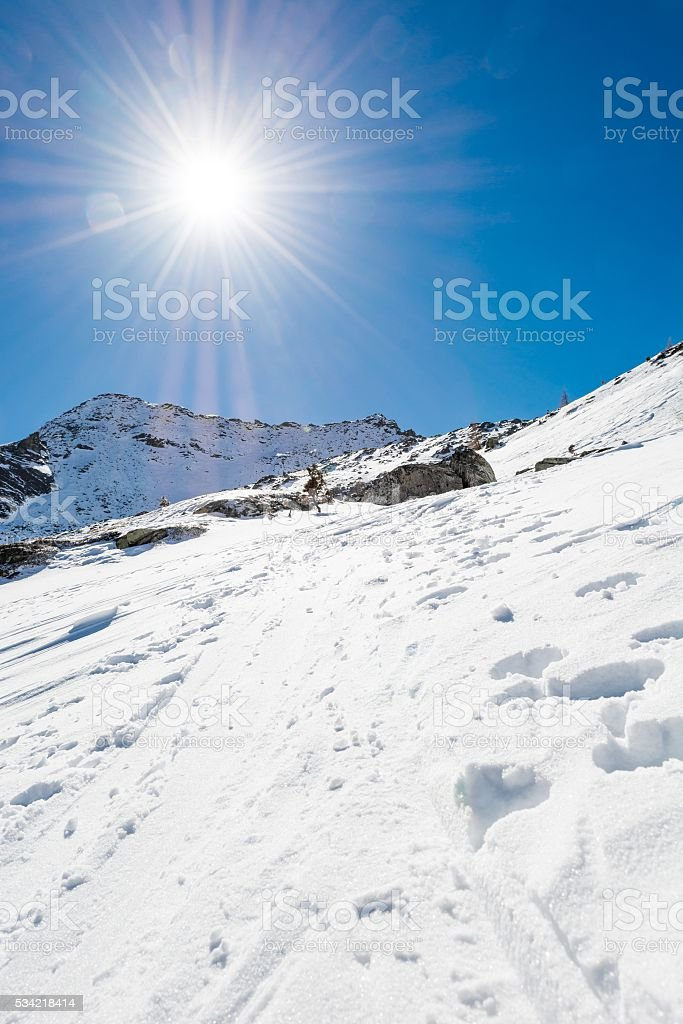 Snow trail ascneding a slope. stock photo