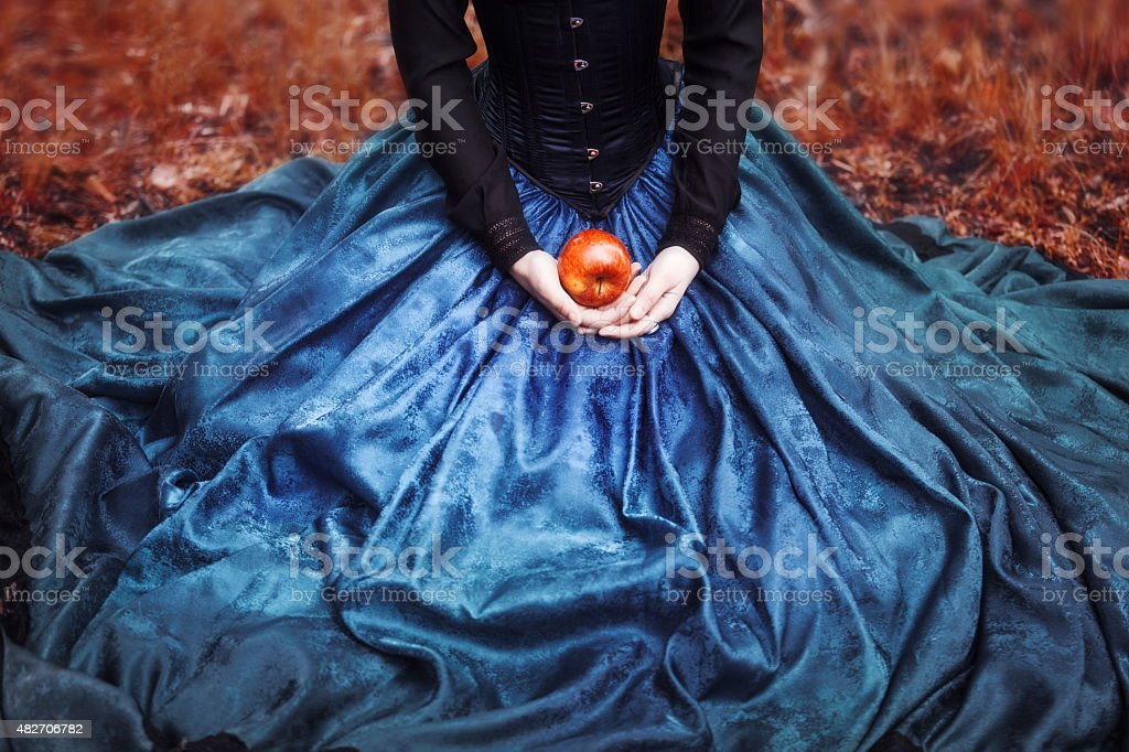 Snow White princess with the famous red apple. Girl holds stock photo