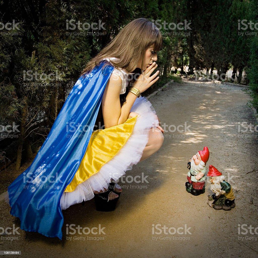Snow White Whispering to Garden Gnomes on Pathway stock photo