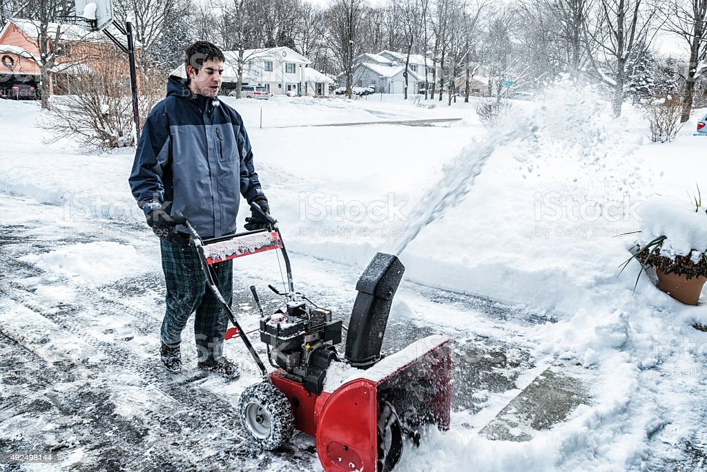 Snowblower Blowing Snow From Frozen Suburban Driveway stock photo