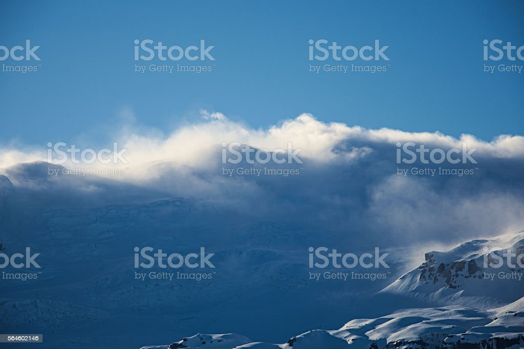 Snow-blown mountain chain at sunset stock photo
