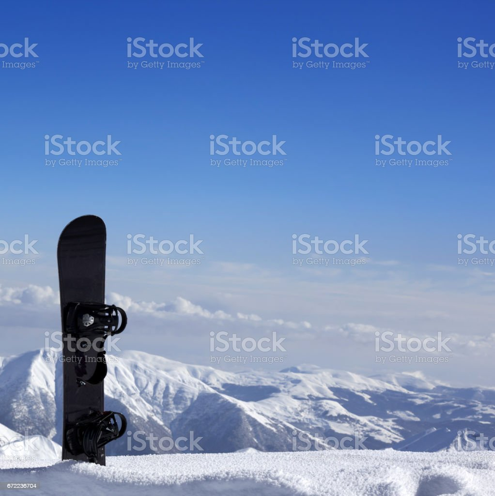 Snowboard in snow near off-piste slope in sun day stock photo