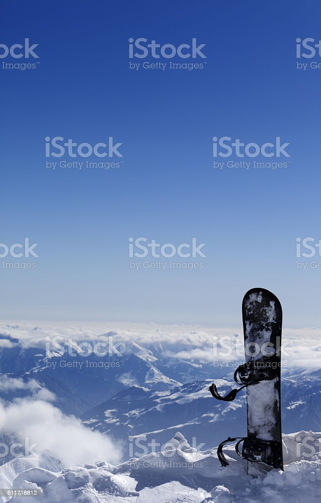 Snowboard in snow on off-piste slope at sun day stock photo