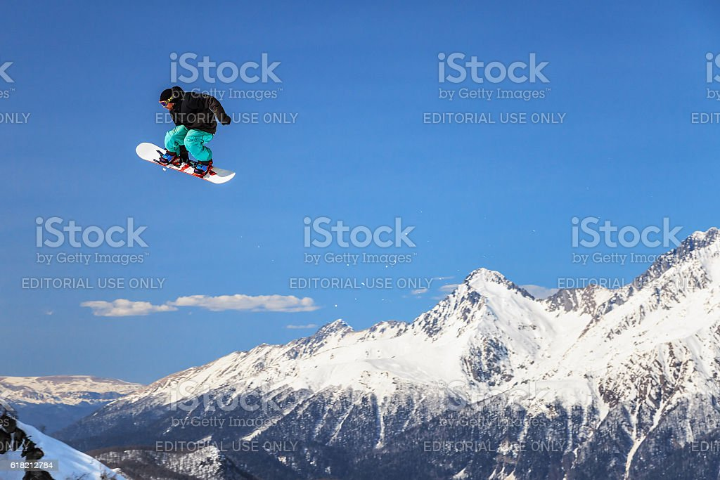 Snowboard rider flying from a ski jump stock photo