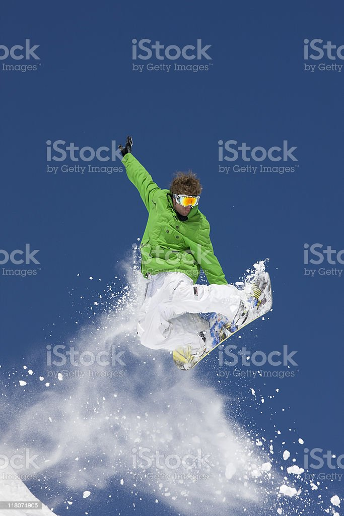 Snowboarder Airborne Against Blue Sky and Powder Snow royalty-free stock photo