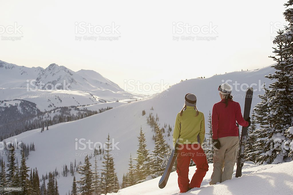 Snowboarder and skier in the mountains stock photo