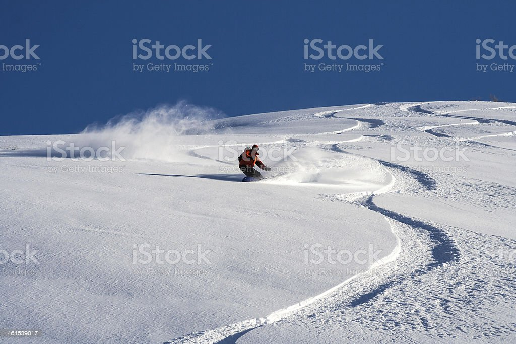 Snowboarder crisscrossing down a powdery slope on sunny day stock photo