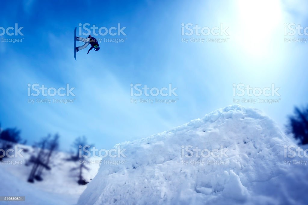 Snowboarder doing a stunt high in the air stock photo