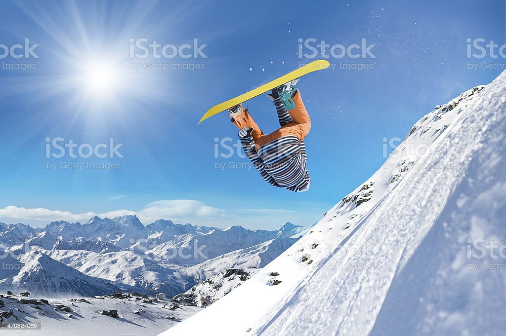 Snowboarder doing flip on steep slope stock photo