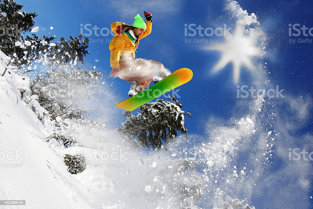 Snowboarder doing impressive jump against a sunny blue sky stock photo