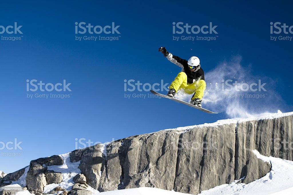 Snowboarder Dropping Off Short Cliff Against Blue Sky stock photo