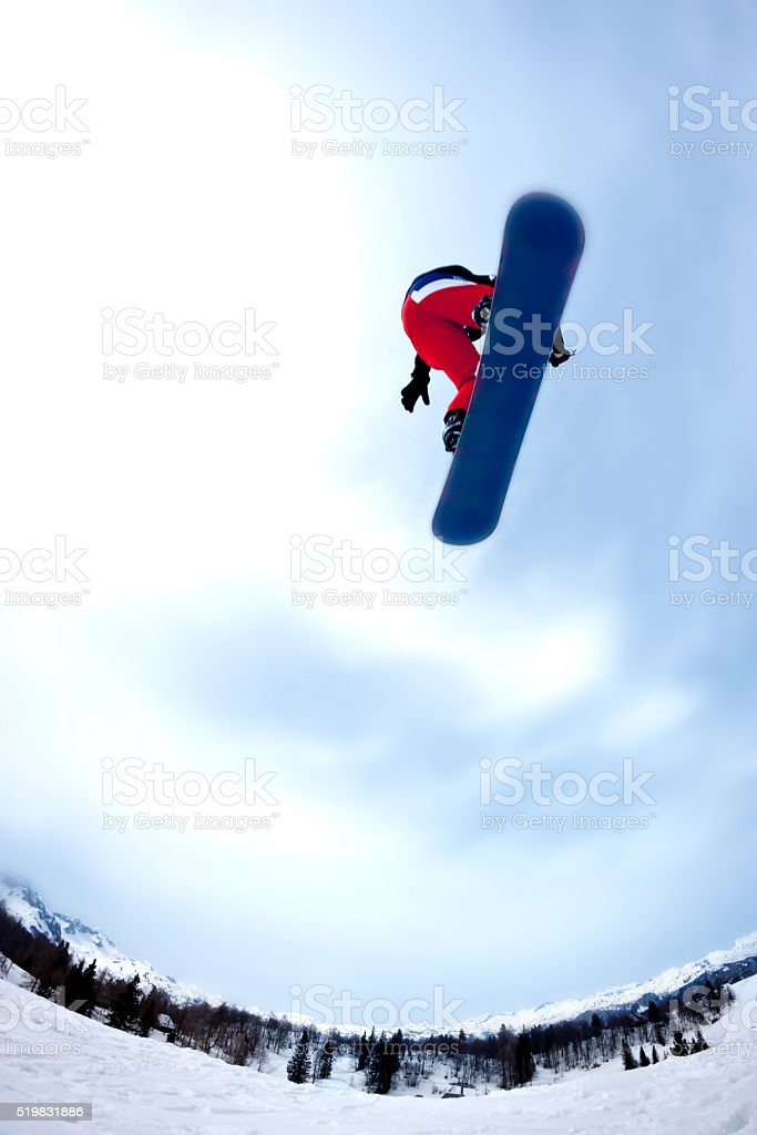 Snowboarder flying over, low angle view stock photo