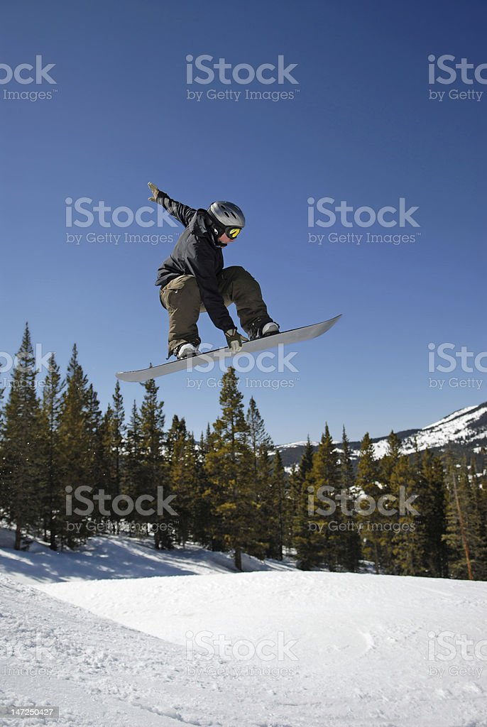 Snowboarder getting air off jump in terrain park stock photo