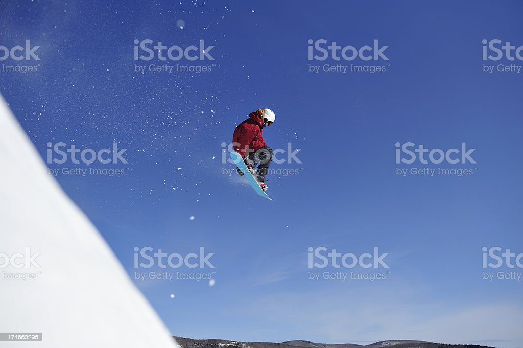 Snowboarder goes off a cliff against blue sky stock photo