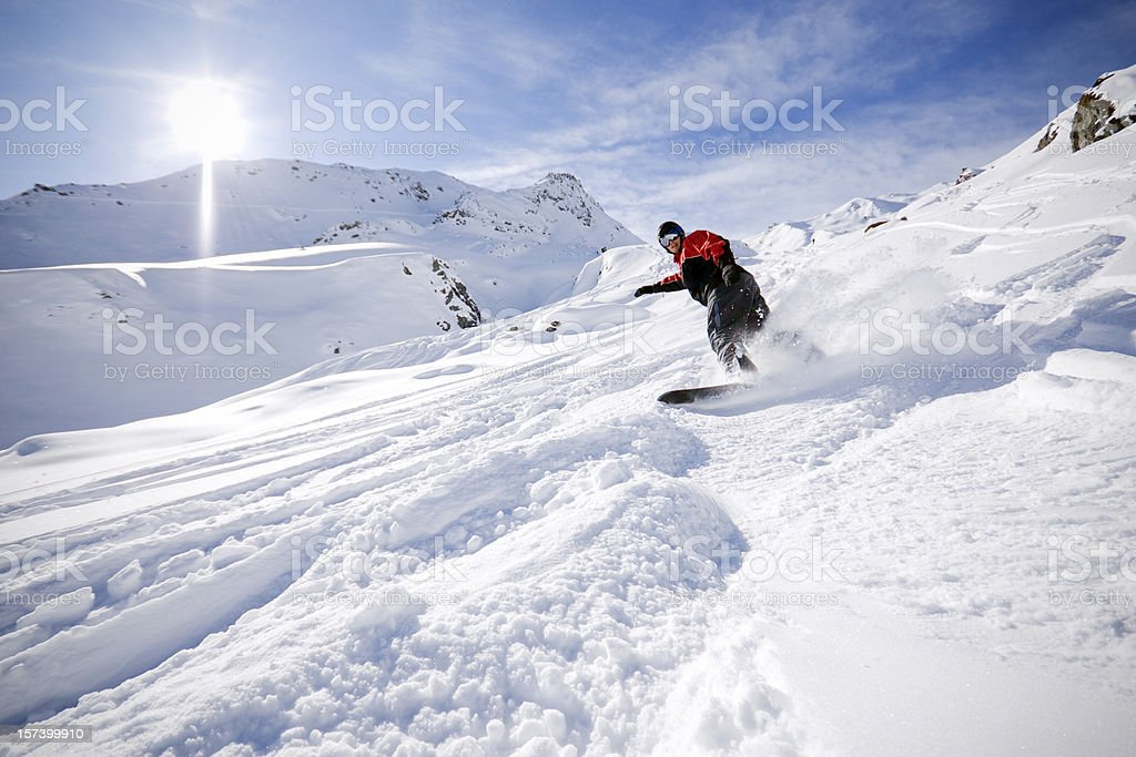 A snowboarder going downhill in the snow in the Alps stock photo