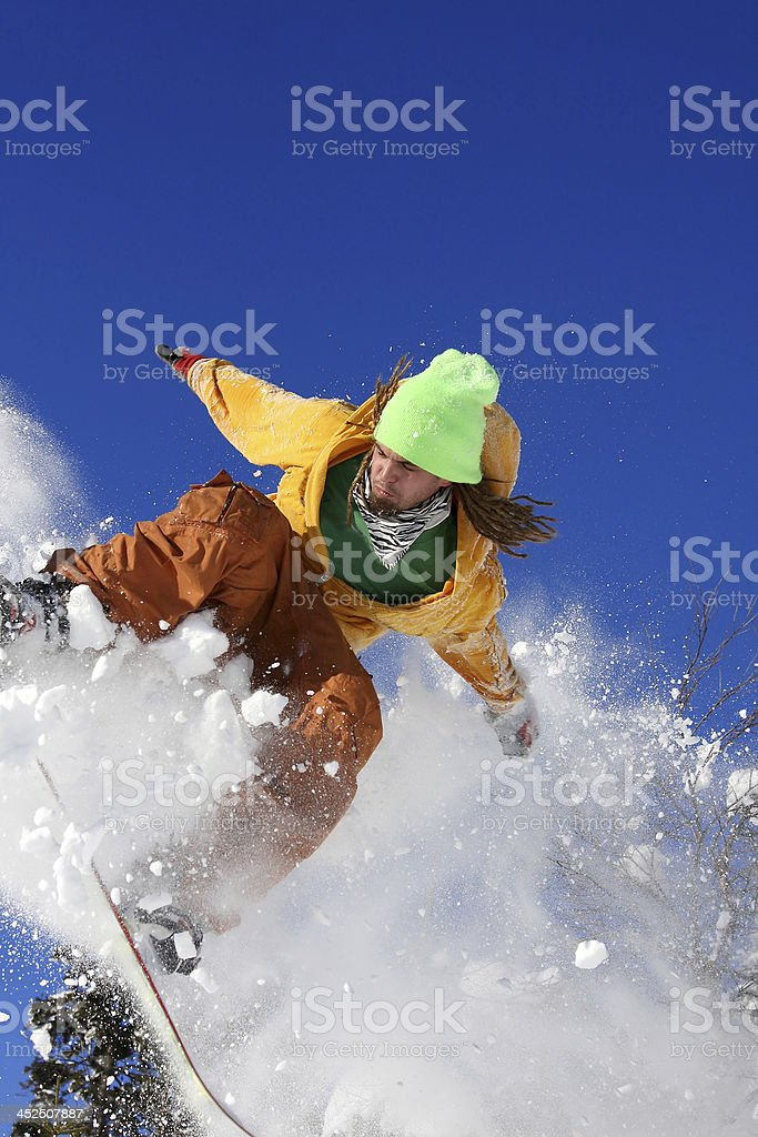Snowboarder in a dust of white snow powder balancing stock photo