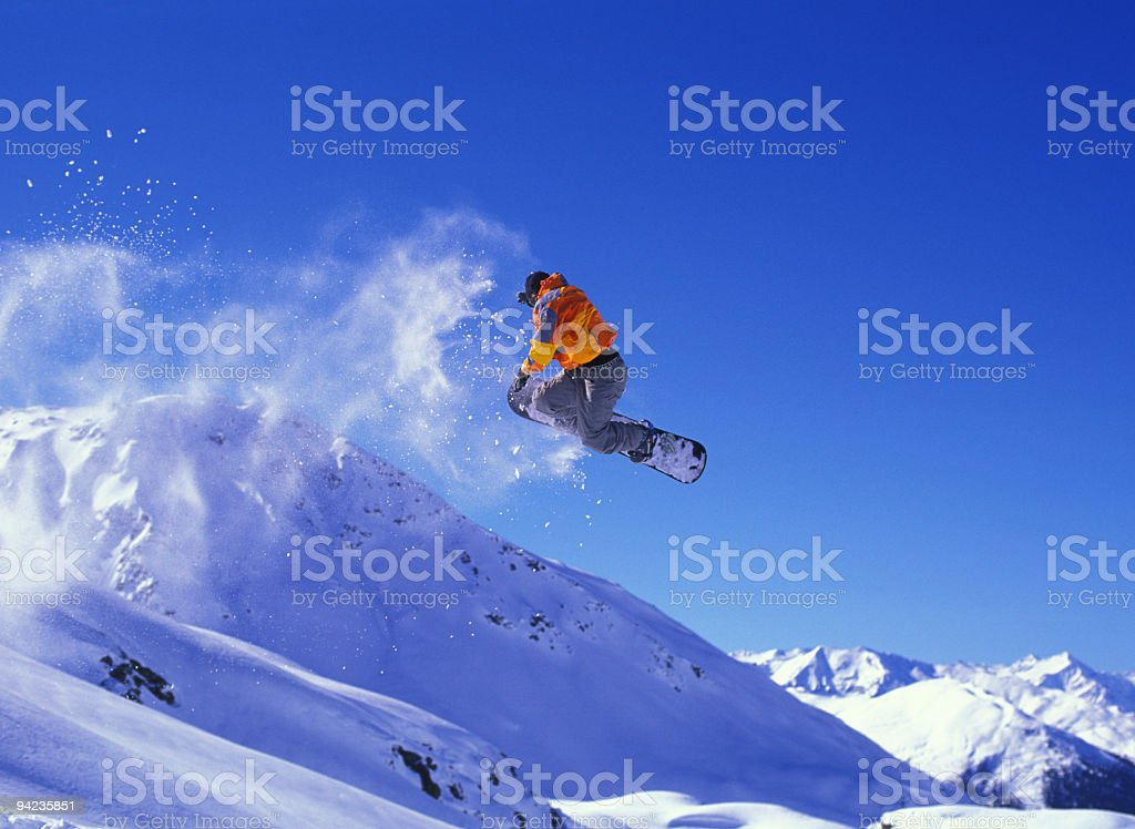 Snowboarder in mid-jump with a cloud of snow trailing behind stock photo