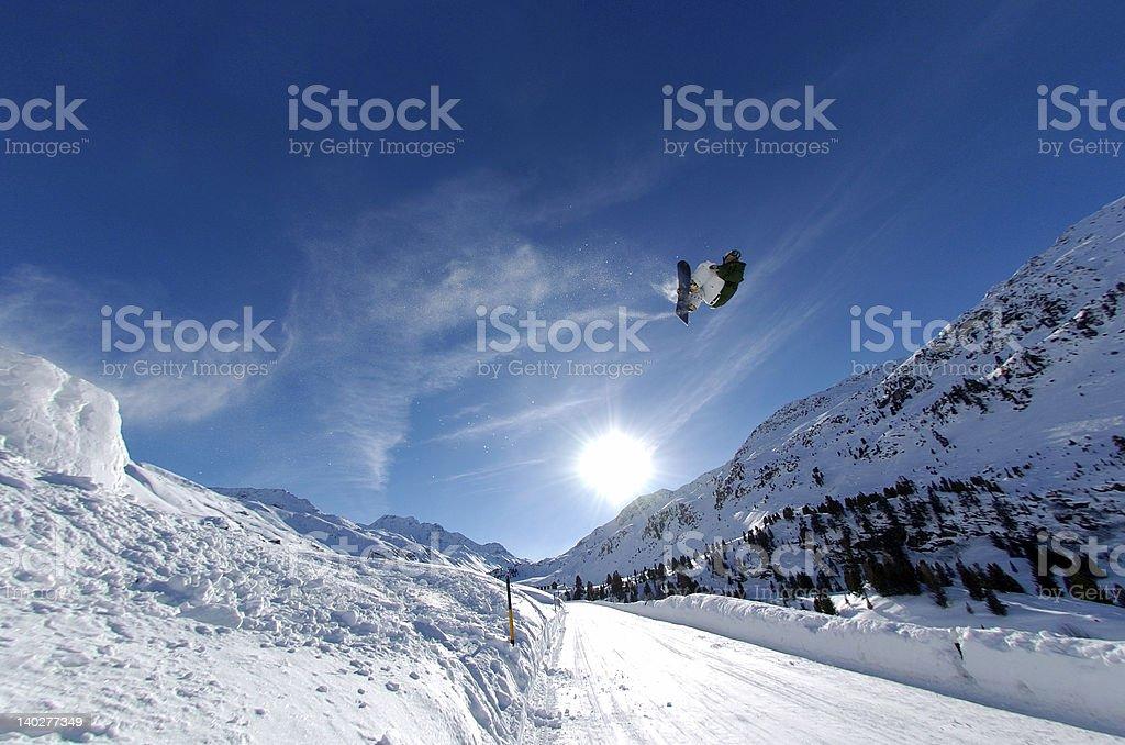Snowboarder jumping across a street gap stock photo