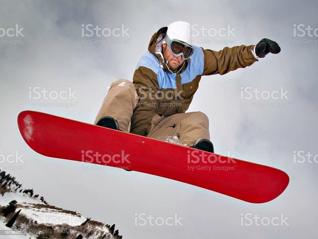 Snowboarder jumping and grabbing board royalty-free stock photo