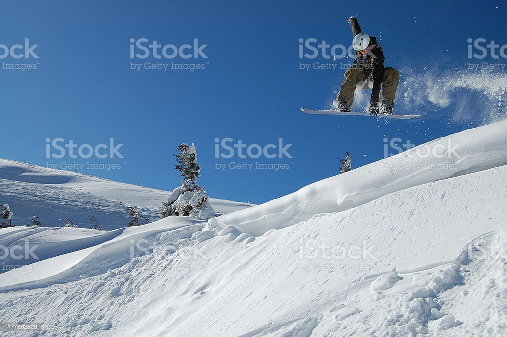 Snowboarder jumping from a cliff royalty-free stock photo