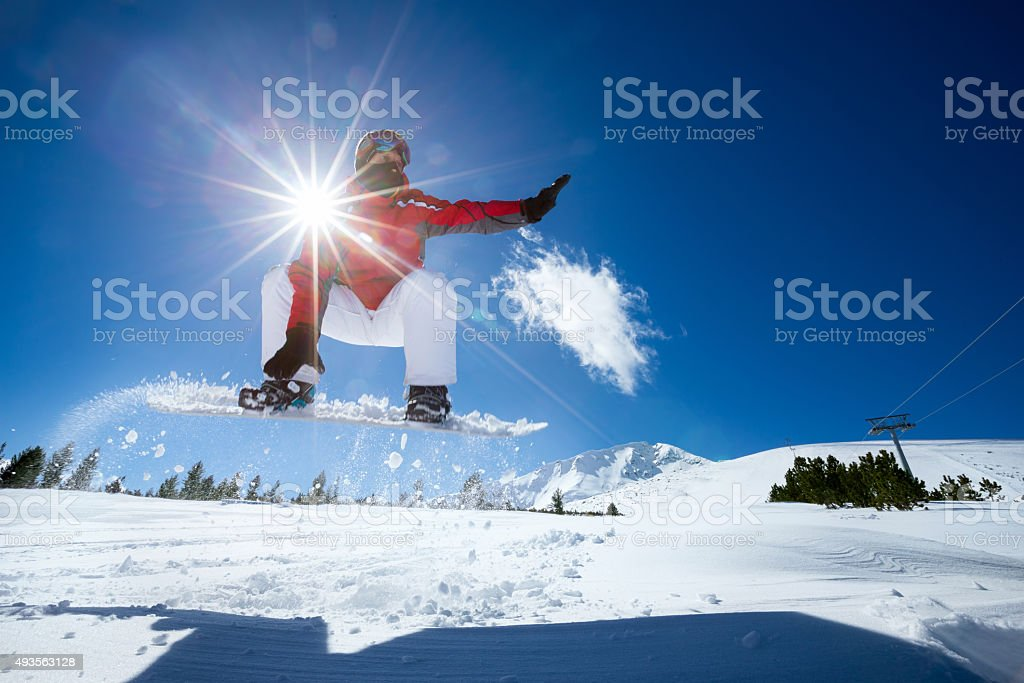 Snowboarder jumping in air stock photo