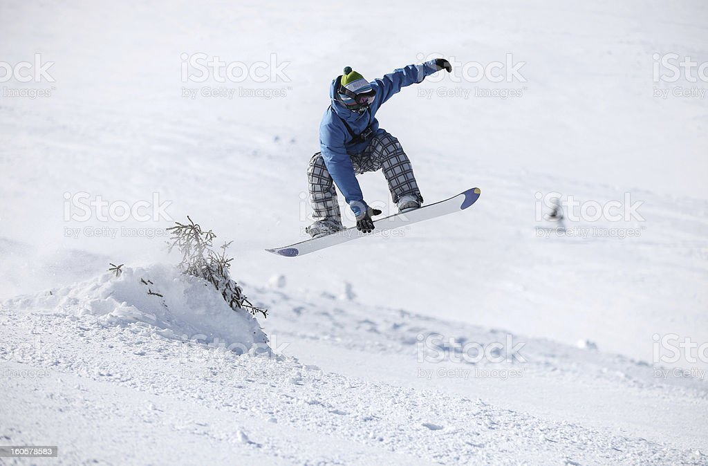 Snowboarder jumping on a snowy slope royalty-free stock photo