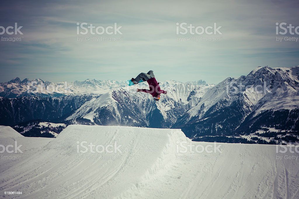snowboarder jumps a backflip stock photo