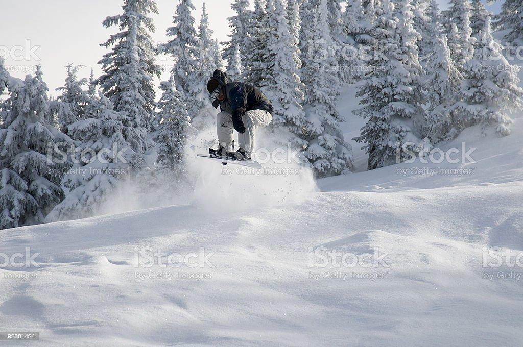 Snowboarder jumps above fresh powder snow. stock photo