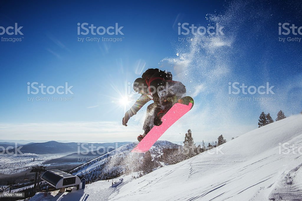 Snowboarder jumps on blue sky backdrop in mountains trick stock photo