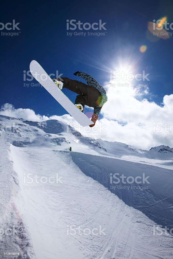 A snowboarder mid air performing a trick jump stock photo