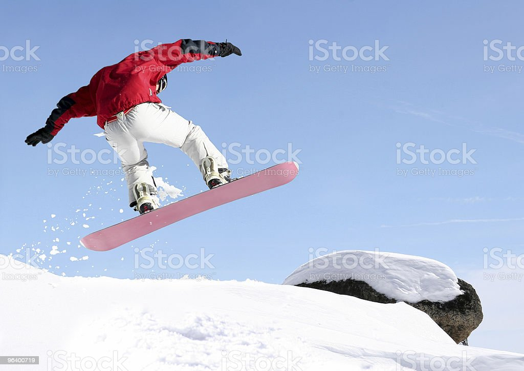 Snowboarder mid-jump with blue sky  royalty-free stock photo