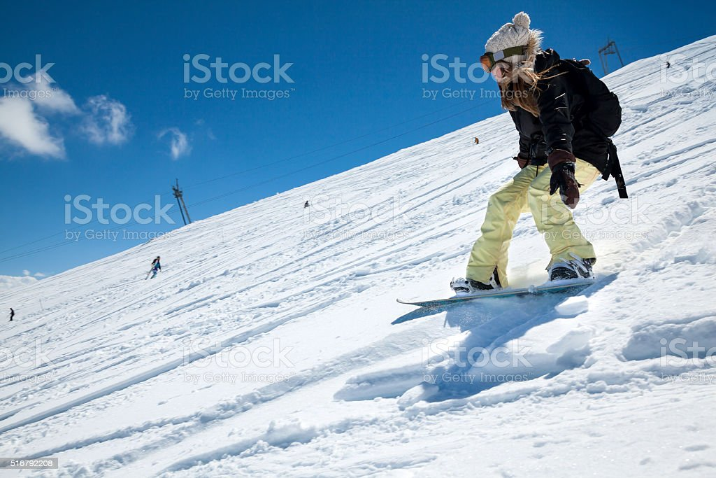 Snowboarder moving down stock photo