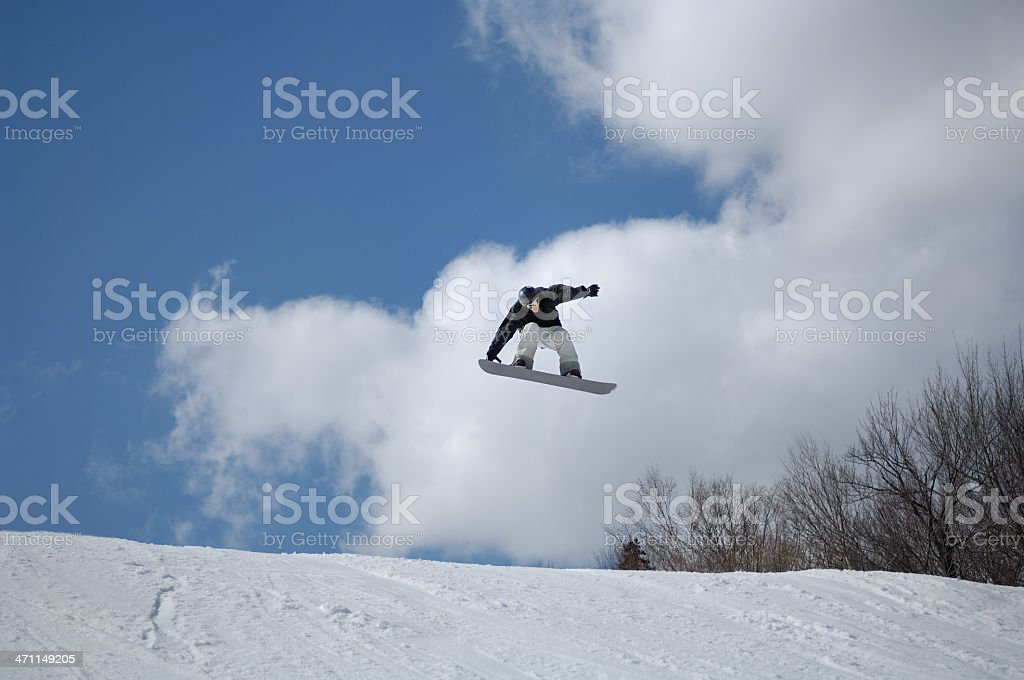 Snowboarder performs a freestyle big air stunt in terrain park stock photo