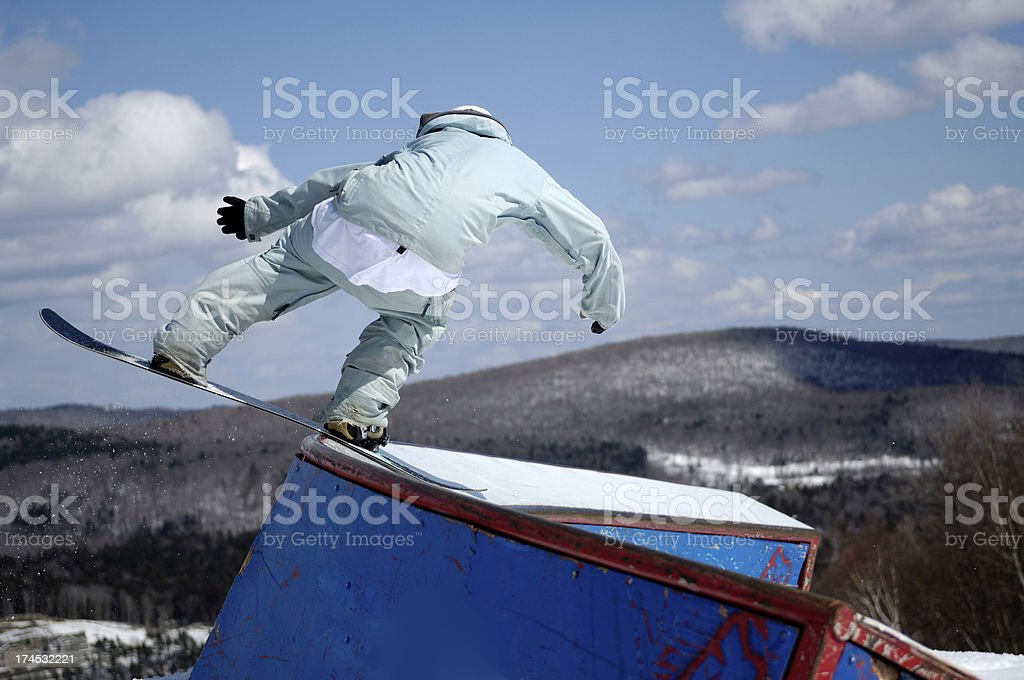 Snowboarder performs freestyle stunt in a terrain park stock photo