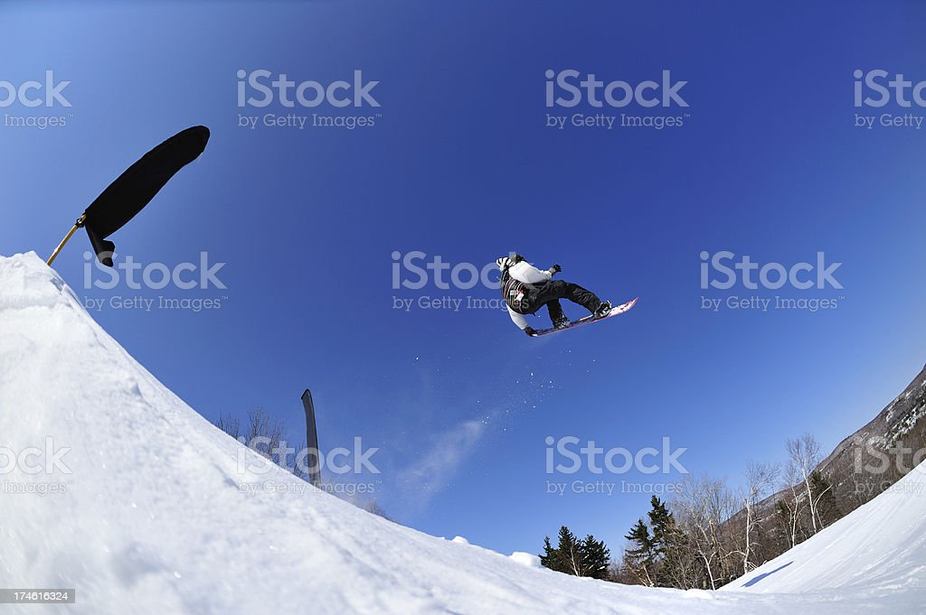 Snowboarder  performs freestyle stunt in terrain park against blue sky stock photo
