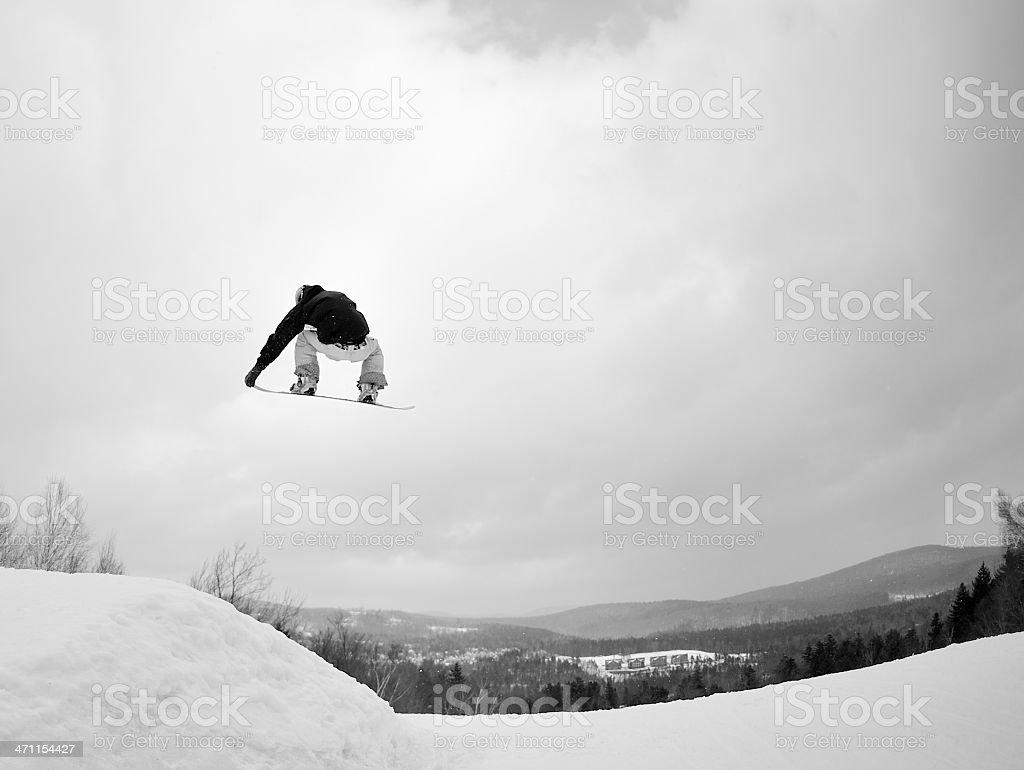 Snowboarder performs freestyle stunt in terrain park black white stock photo