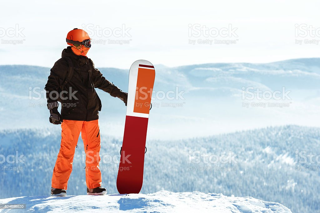 Snowboarder posing snowboard against mountains stock photo