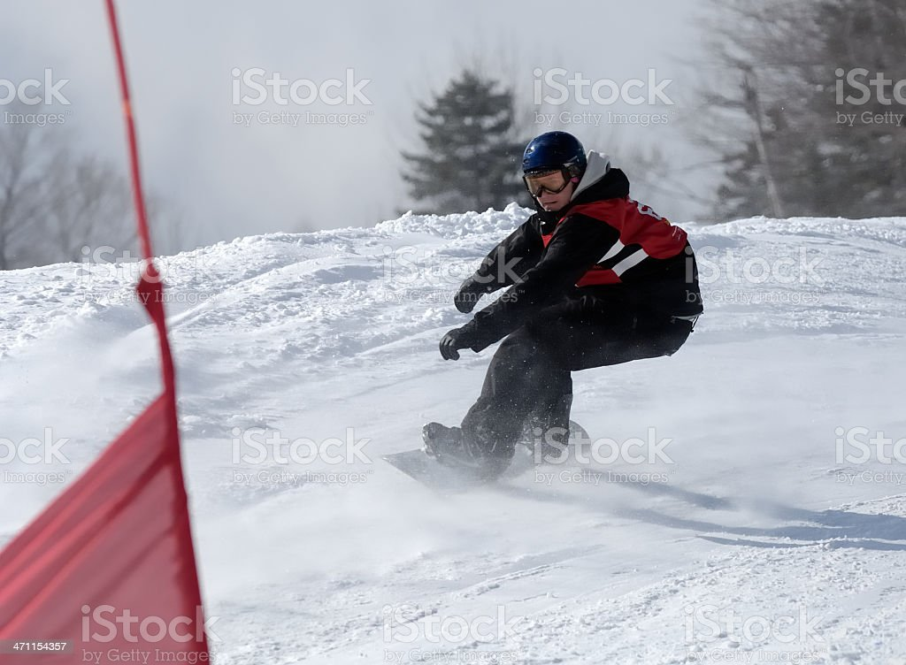 Snowboarder races down a boardercross competition stock photo
