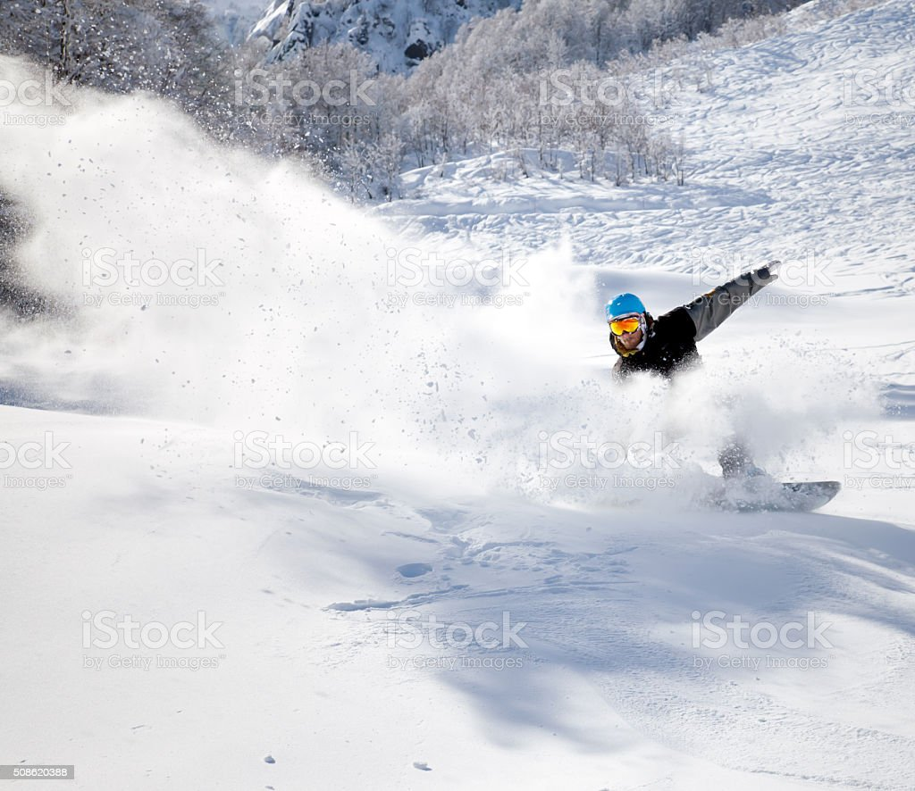 Snowboarder racing down stock photo
