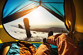 Snowboarder relaxing in tent on background of sunset