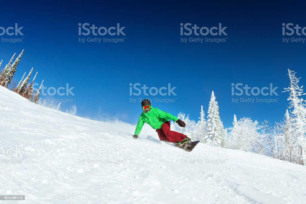 Snowboarder rides on slope snowboarding stock photo